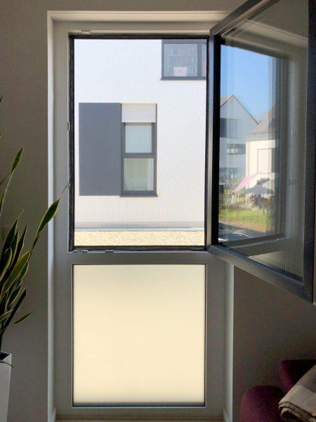 Sichtschutzbeklebung an einem hohen Fenster in einem Wohnhaus
