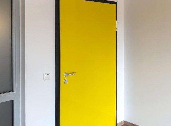 Tür-Vollfolierung - Schwarzer Türrahmen und gelbes Türblatt im Auftrag der Diakonie