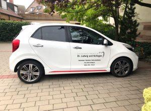 Fahrzeugbeschriftung - Seitenansicht eines weißen Kia Picanto mit neuer Dr. Ludwig Folierung
