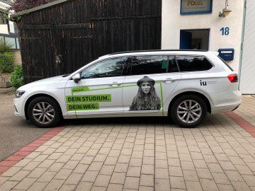 Fahrzeugfolierung - Seitenansicht eines weißen Passat für die UI Internationale Hochschule der frisch foliert wurde