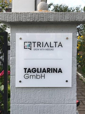 Acrylglas-Schild an einem Gartenzaunpfosten für Trialta